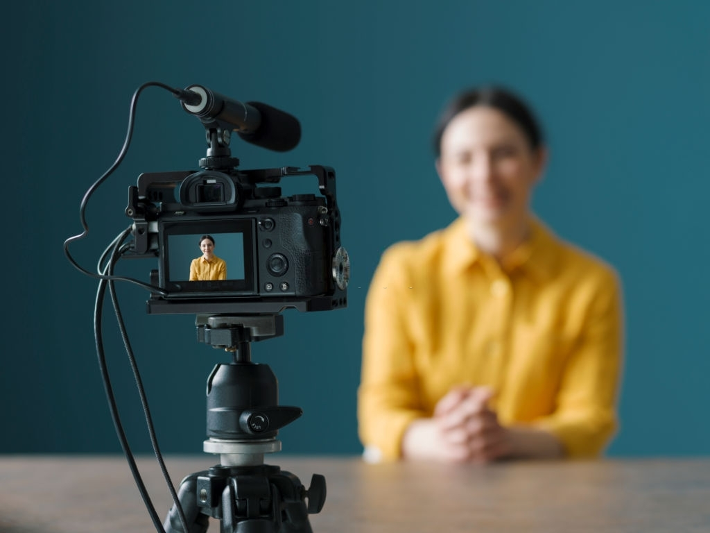 Smiling woman sitting in front of a camera and making a video blog